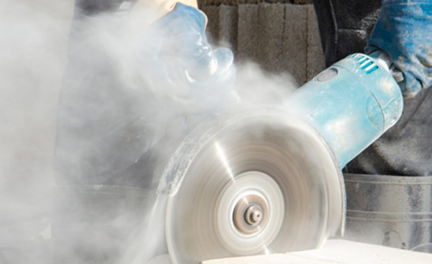 Someone Using a Power Saw on Concrete, Creating Airborne Silica Dust